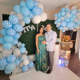 couple at baby shower decorated with balloon arch