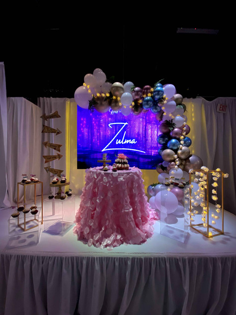 stage decorated with balloon arch and lights