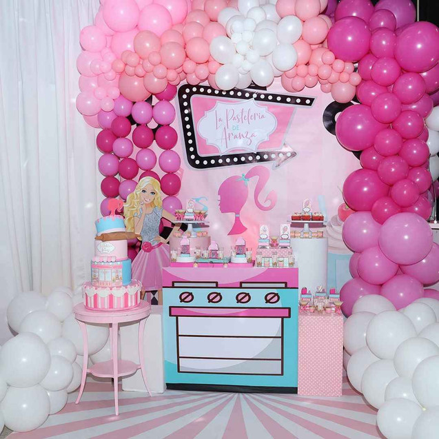 Pink balloons arrangement with a cake and barbie decoration