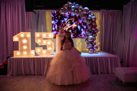 birthday girl posing front a decorated stage