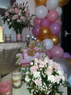 Little wench sitting on a pink chair in a room decorated with white, golden and pink balloons