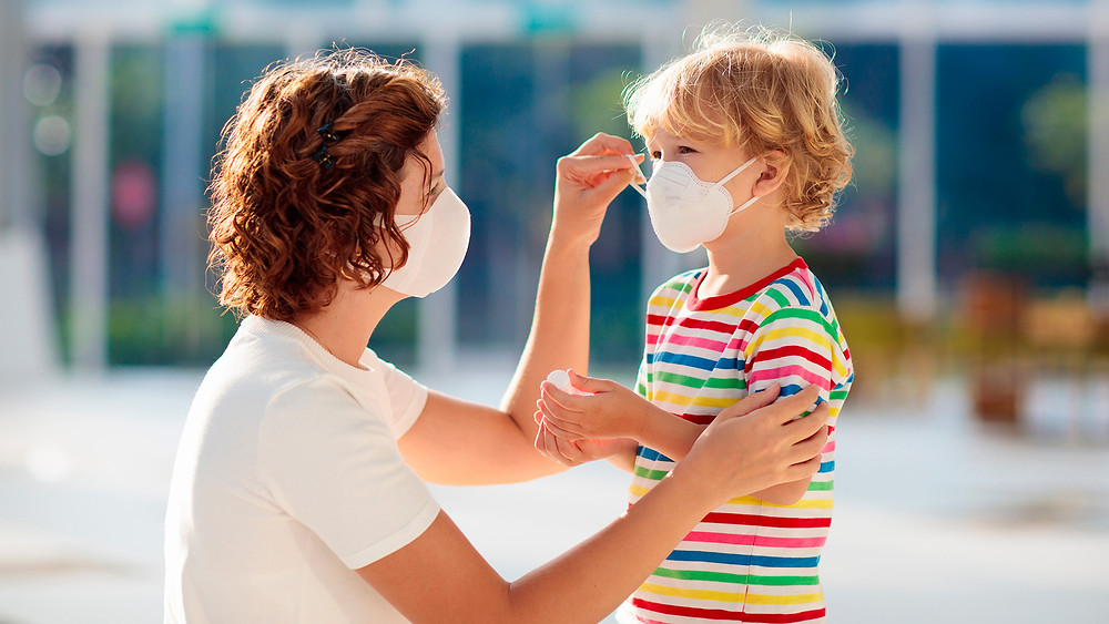 woman-putting-face-mask-on-her-son