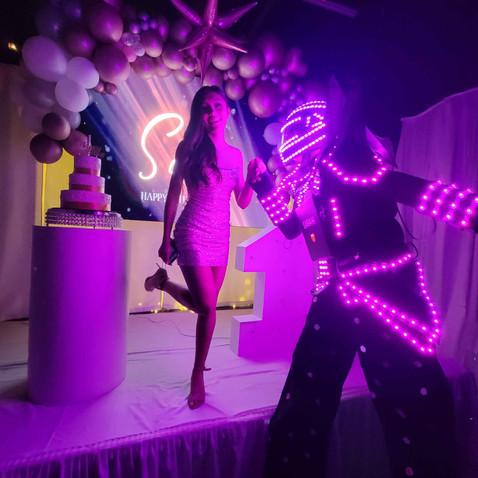 pink led robot kissing birthday girl hand