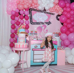 Little girl in a room full of pink balloons arrangements, a cake and barbie decoration