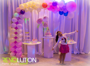 Balloon arrangement behind a little girl  at a party with dim purple light
