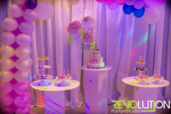 Pink and purple balloon arrangement above 3 tables with candy on top