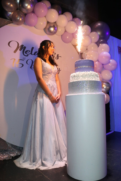 girl with cake blowing out candles-15th-birthday