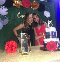birthday girl with her mom posing next to birthday cake