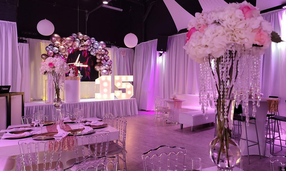 banquet hall decorated with balloons and pink lights