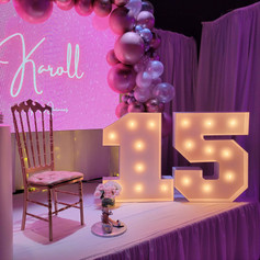 stage with pink balloon arch on 15th birthday