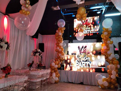 grey and yellow balloon arrangement on the sides of the stage in a party venue