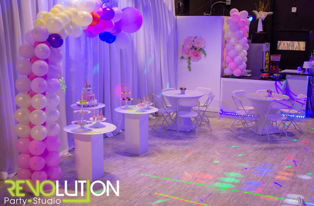 Purple decorated event venue with balloon arrangements and light show