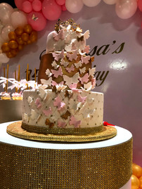 White, pink and golden decorated cake with butterflies in a 15 birthday party venue in Kendall Miami
