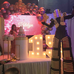 led robot next to stage with birthday girl