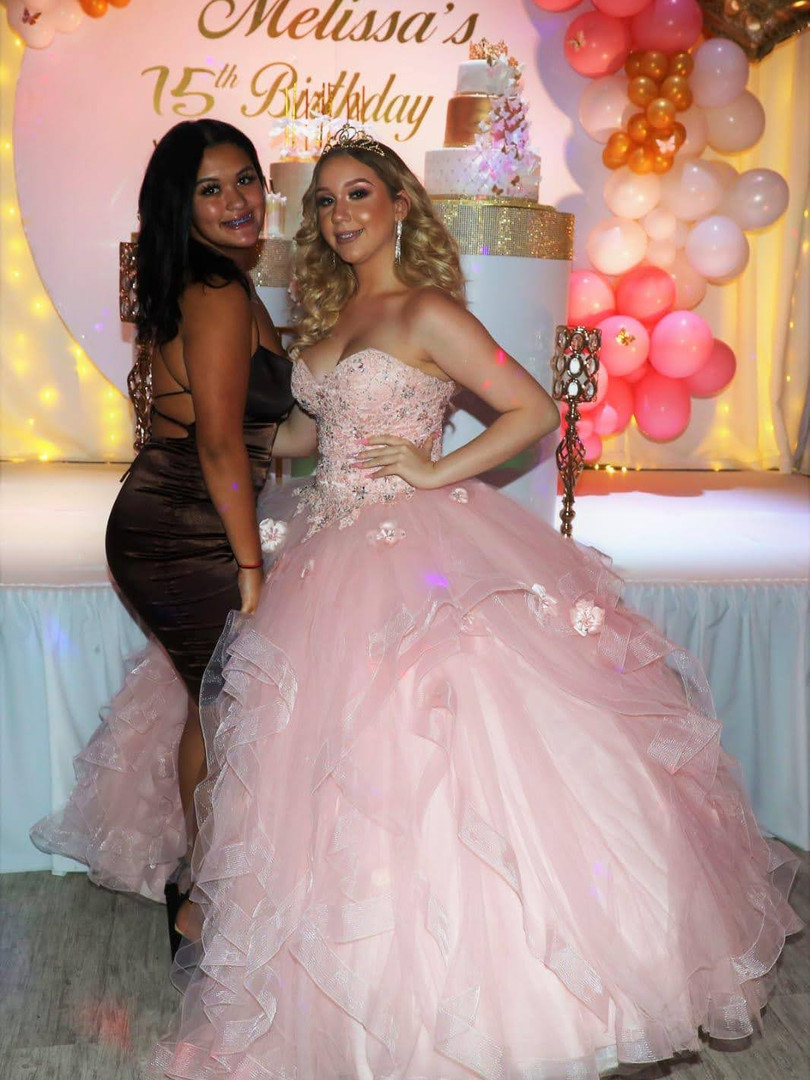 Two womans posing for a photo in a party venue