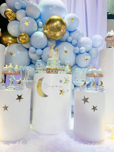 Table with double tier cake and candies, blue and gold baby shower