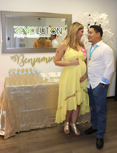 pregnant woman with her couple posing in front of baby shower decoration