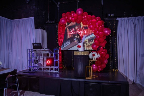 stage with red balloon arch and black decoration