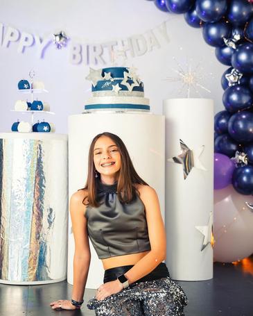 girl with cake balloon arrangement birthday party