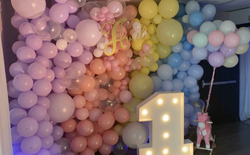 "Multi color balloon arangement behind a ""1"" sign"