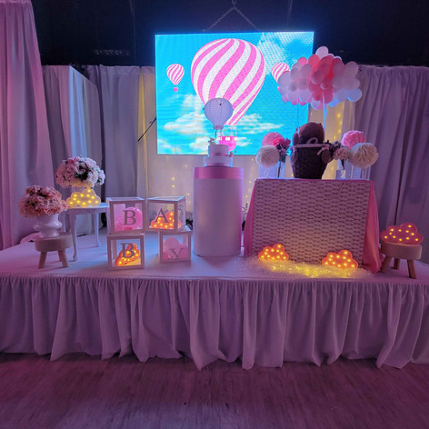 stage decorated with pink balloons in baby shower