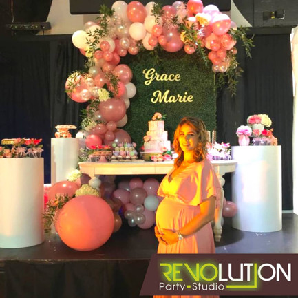 Pregnant girl in front of pink and white decoration baby shower