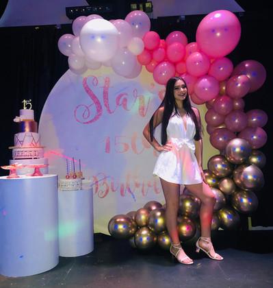 birthday girl posing front arrangement of balloons