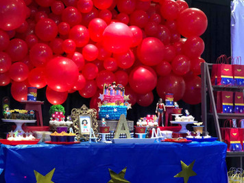 Red balloons arrangement above a blue table with cake on top