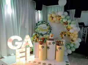 """Gael"" sign in a event venue with a green, yellow and white balloon arrangement"