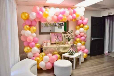 White, pink and golden balloon arrangement in a room with white sofas