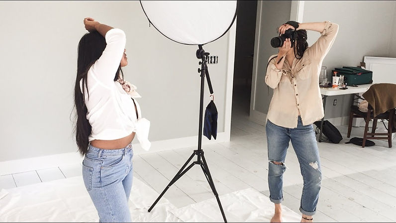 Woman taking a photo to another woman with a white shirt