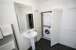 washer and dryer concealed in bathroom cupboard