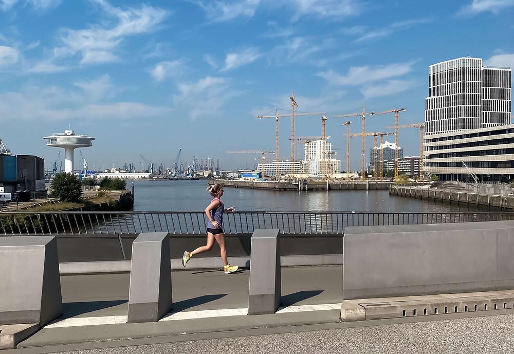 Nele läuft in der Hafencity in Hamburg. Im Hintergrund ist die Elbphilharmonie