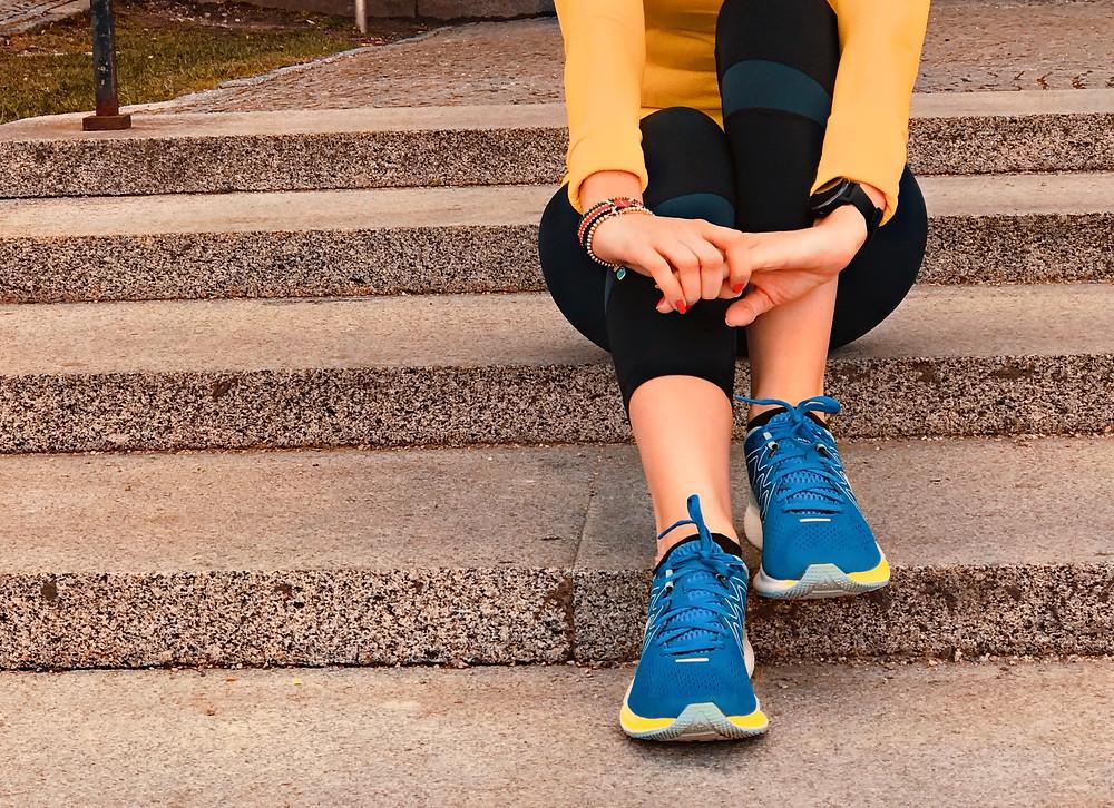 Nele sitzt in Sportkleidung auf der Treppe