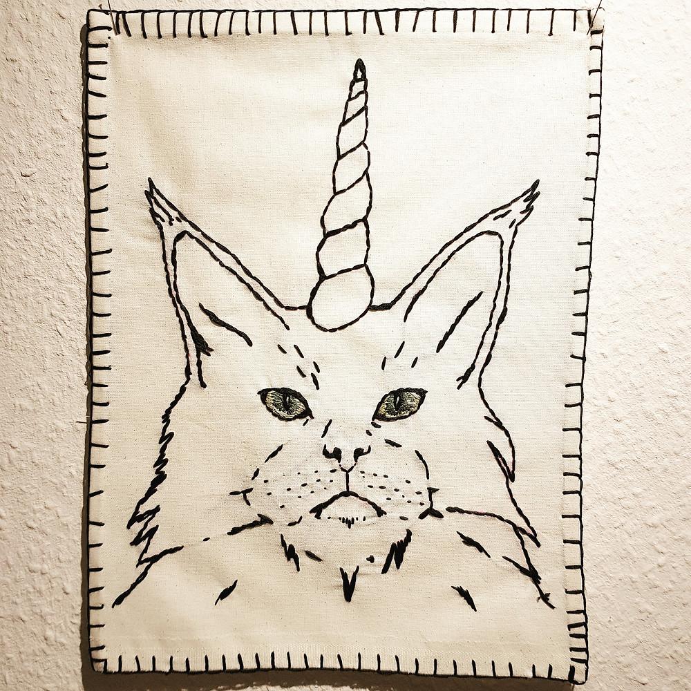 Portrait einer Katze mit einem Horn als bestickter Wandbehang