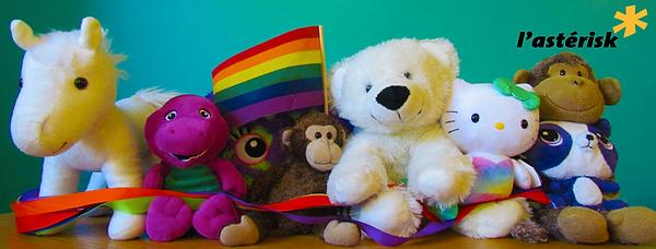 des jouets en peluche avec un drapeau arc-en-ciel