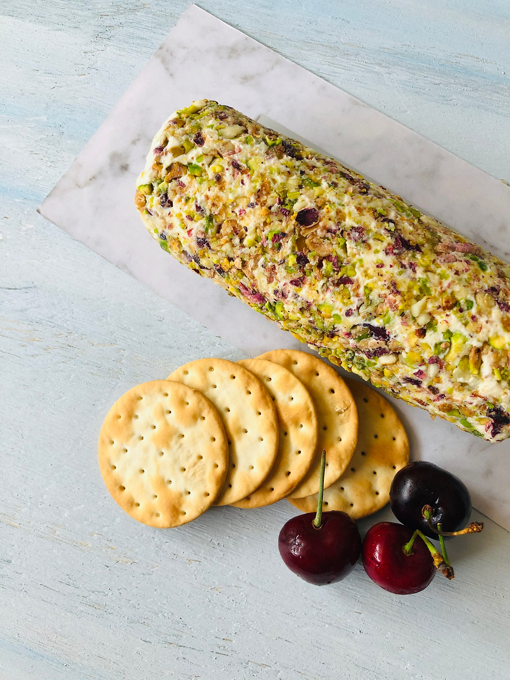 Philadelphia cream cheese log with dried cranberries and pistachios, crackers and cherries
