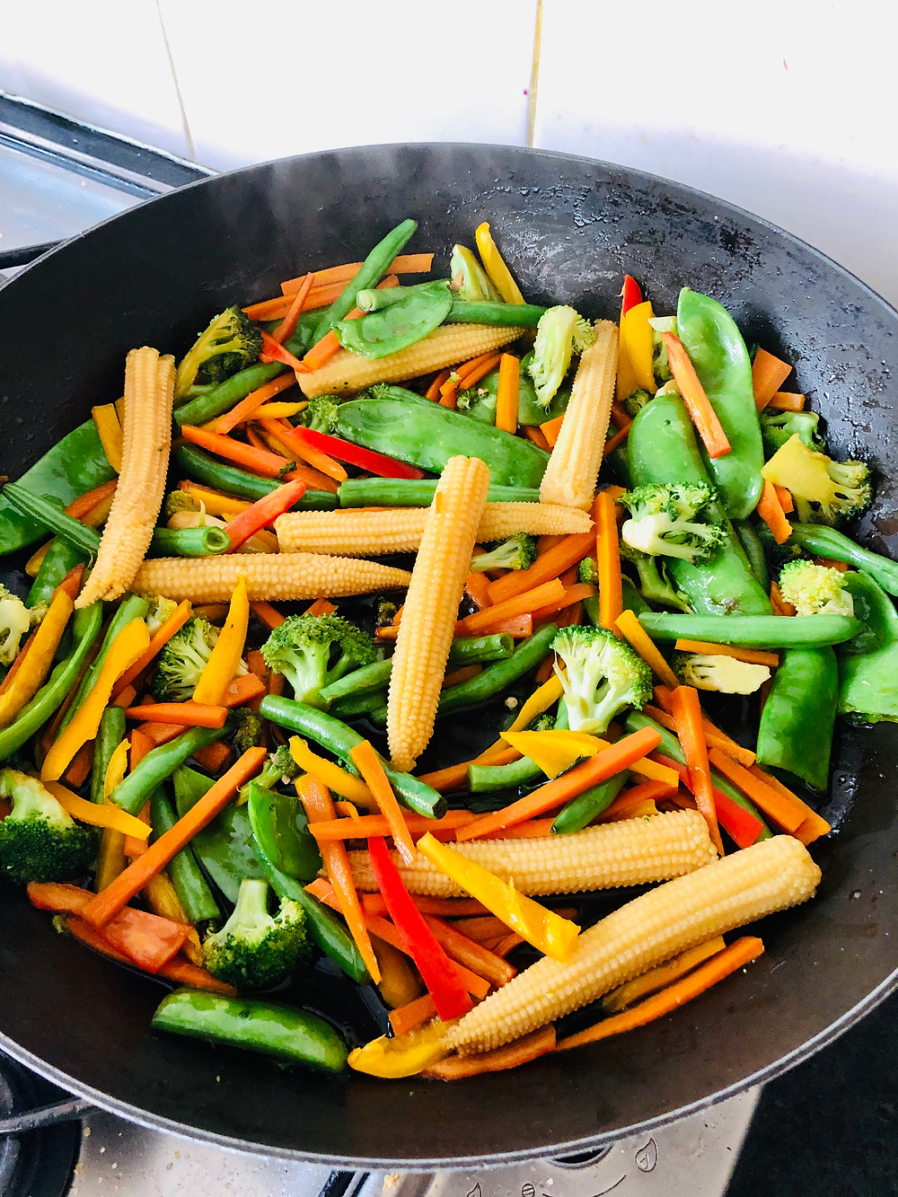 Corn, broccoli, peas, beans, capsicum stir fried in a pan with Japanese sauce