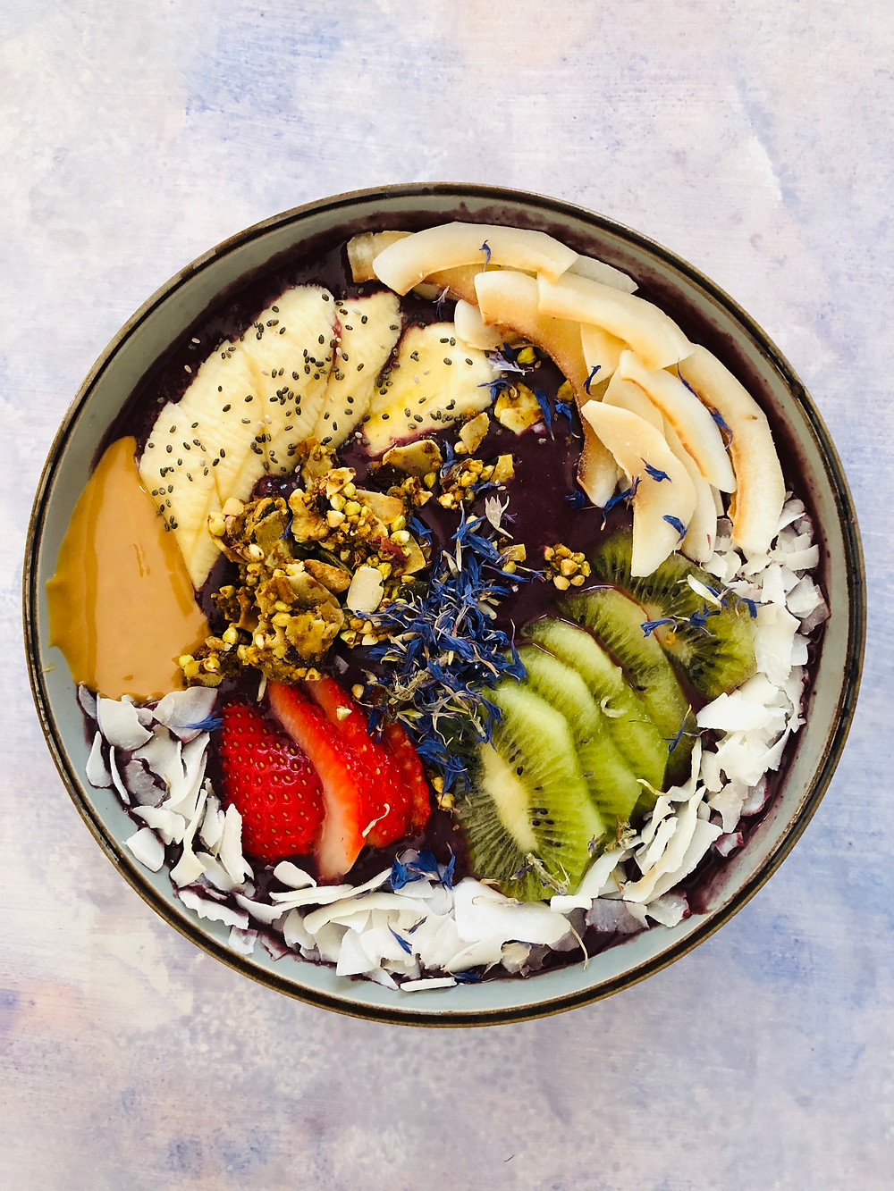 Colorful açaí bowl with banana, kiwi, strawberry, edible flowers, peanut butter and nuts