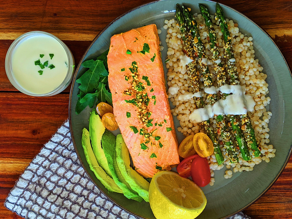 Baked salmon on a plate with couscous, asparagus, dukkah seasoning and yoghurt sauce