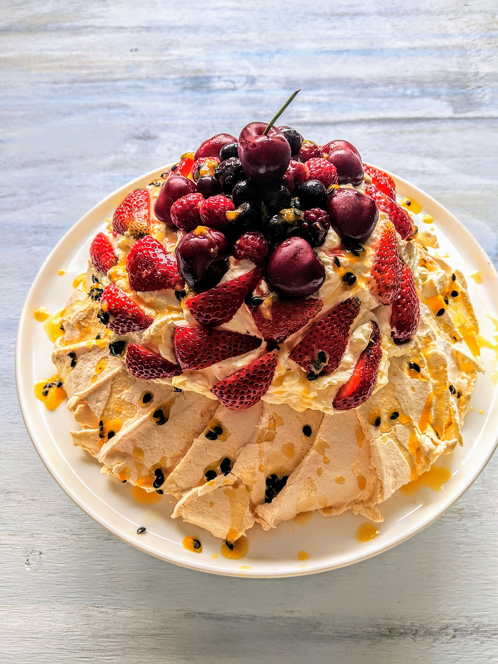 Pavlova cake with strawberries, passiofruit and cherries on top