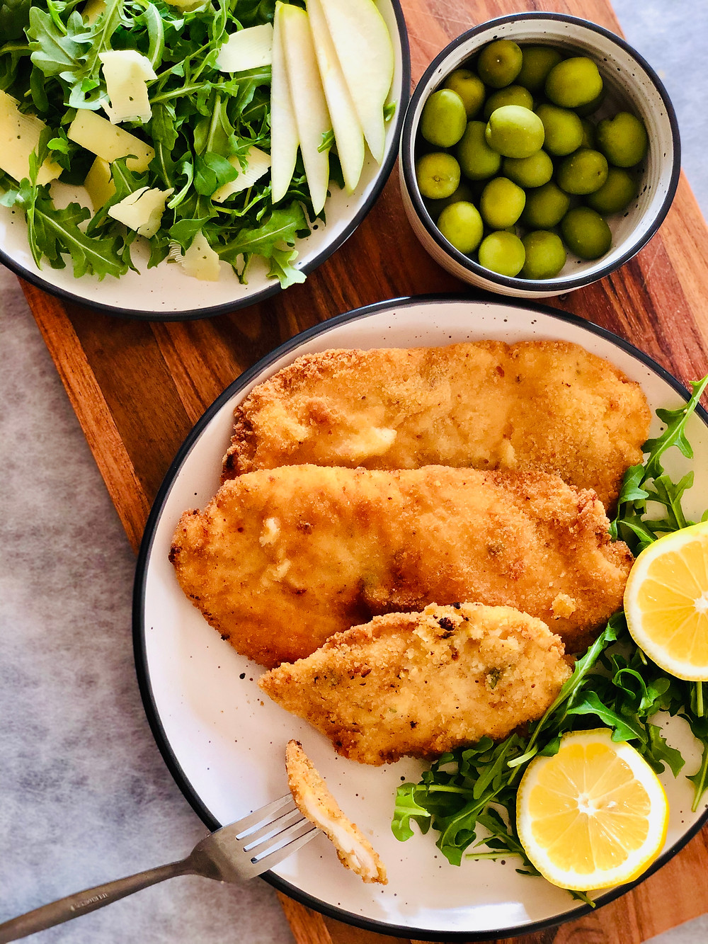 Chicken schnitzel on a plate with lemon, olives, and a small salad