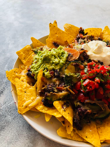 Nachos plate with corn chips, beans, meat, guacamole, salsa, sour cream and veggies