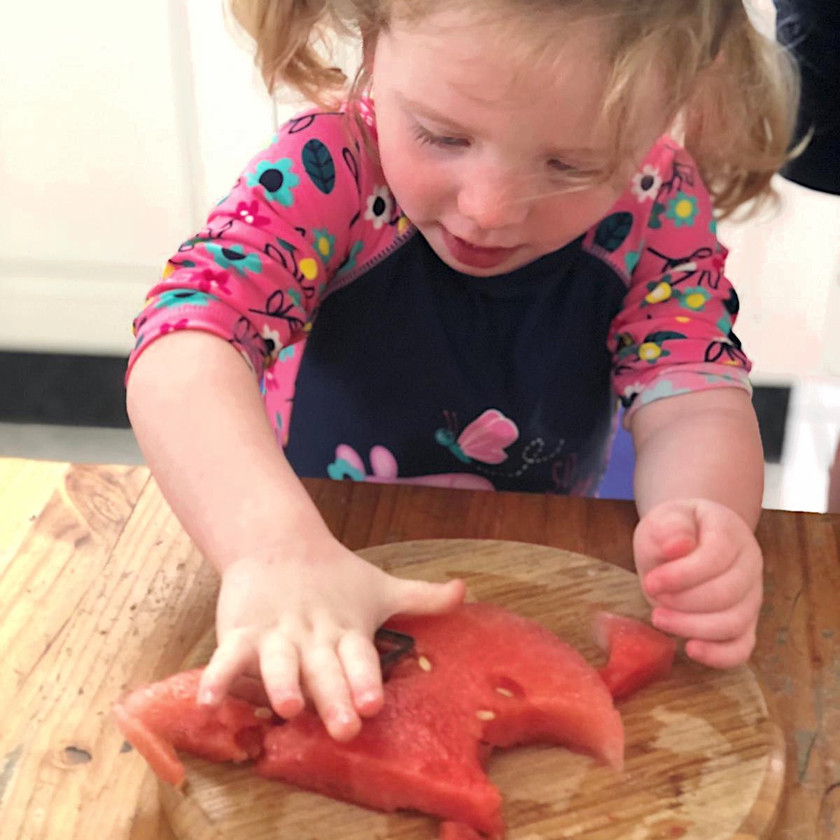 Toddler using cookie-cutter to cut shapes from watermelon