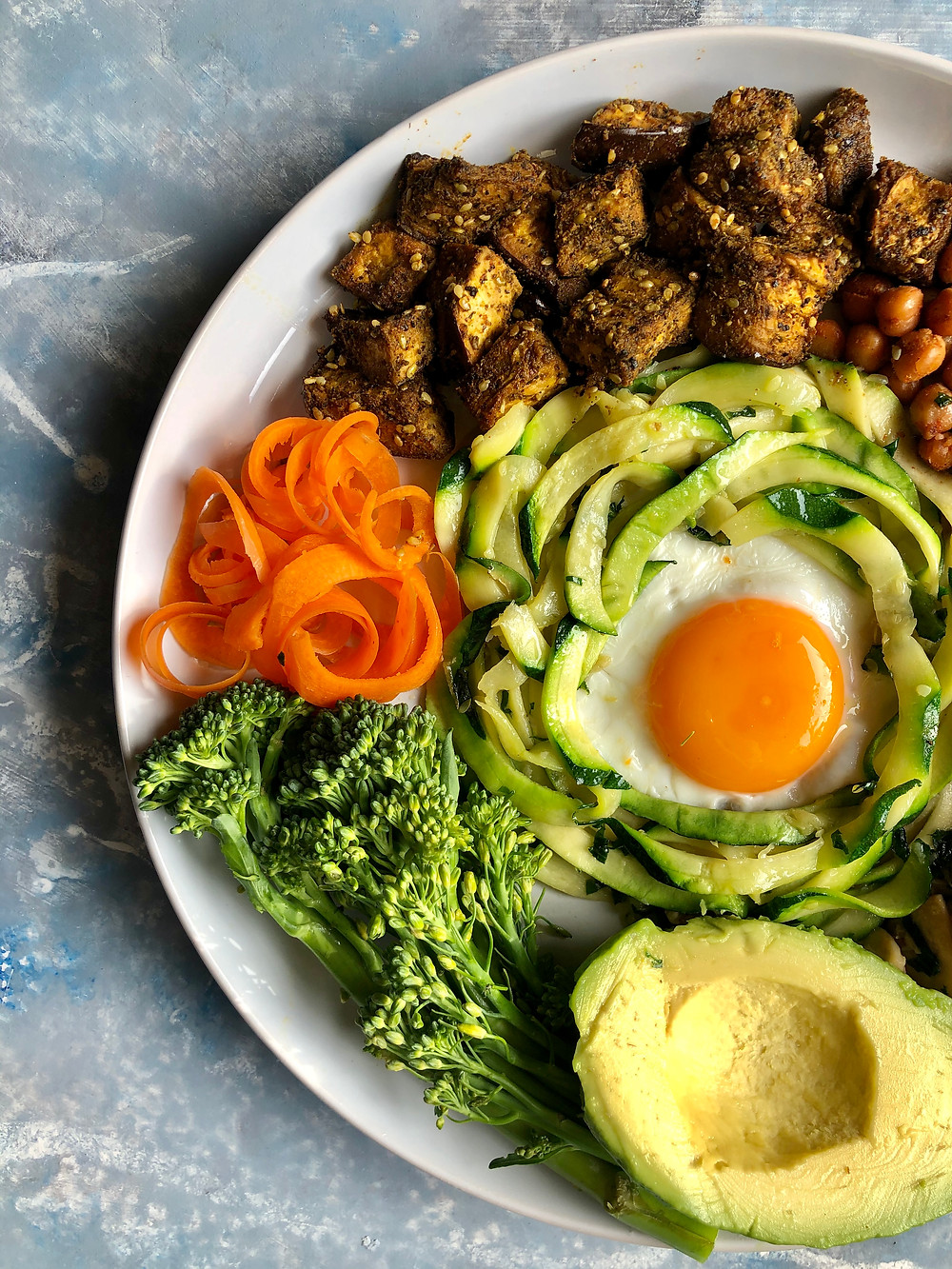 Breakfast plate with eggplant, chickpeas, carrots, zucchini, chickpeas, broccolini, avocado and egg