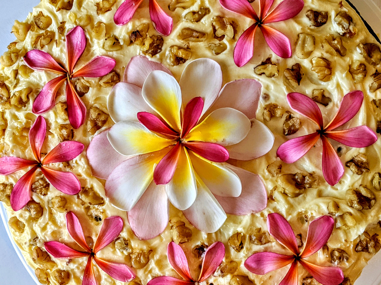 Close up of carrot cake with frosting and flower decoration