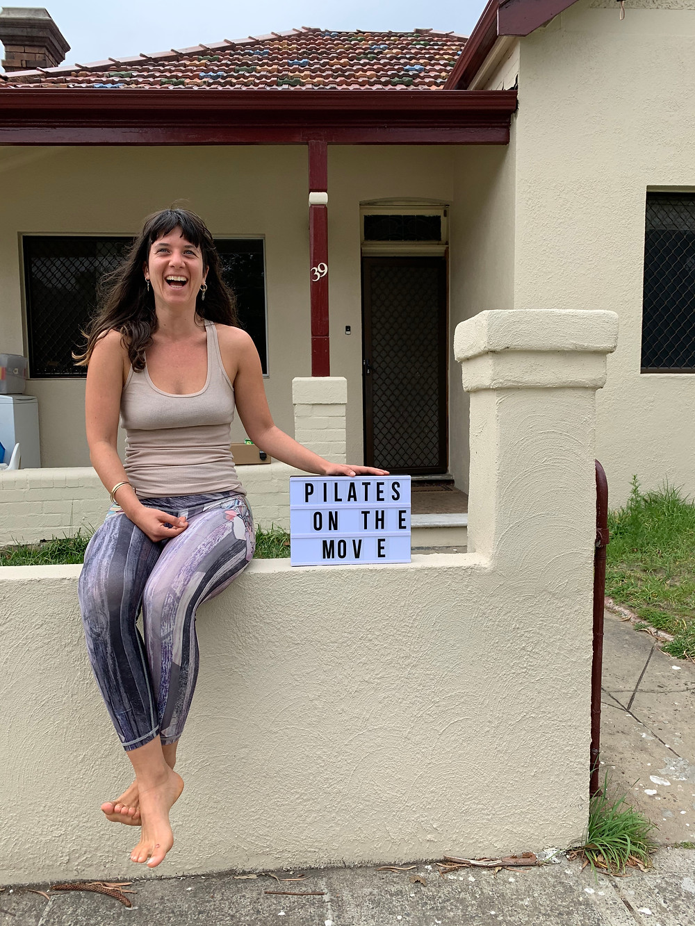 """Shira sitting outside on the move studio smiling and holding a sign that says """"pilates on the move"""""""
