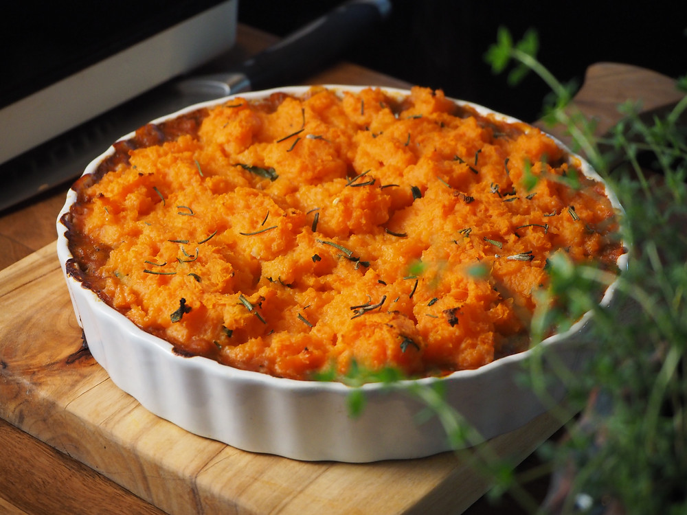 A vegan lentil shepherd's pie, topped with sweet potato mash and herbs, sits atop a wooden chopping board.
