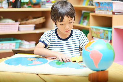 little boy playing with puzzle of map.j