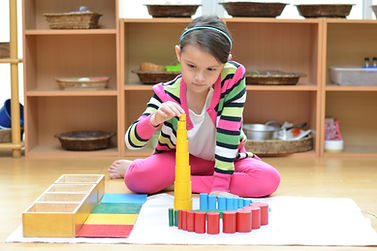 Little girl hand building tower made of